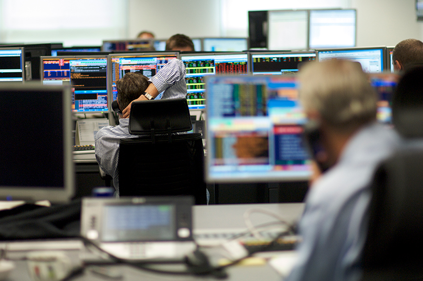 Traders using telephones in front of market data screens