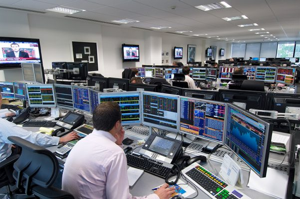 financial trader looks at screens