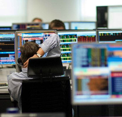 financial trader on phone with screens