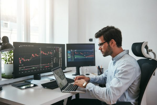 financial trader working with screens at home